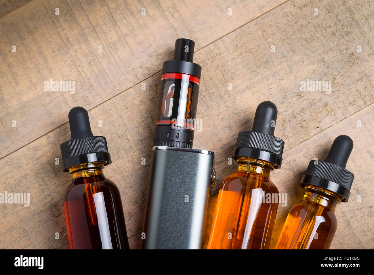 Vaping mod e-cig with tank atomizer and juice bottles over wood background - Stock Image