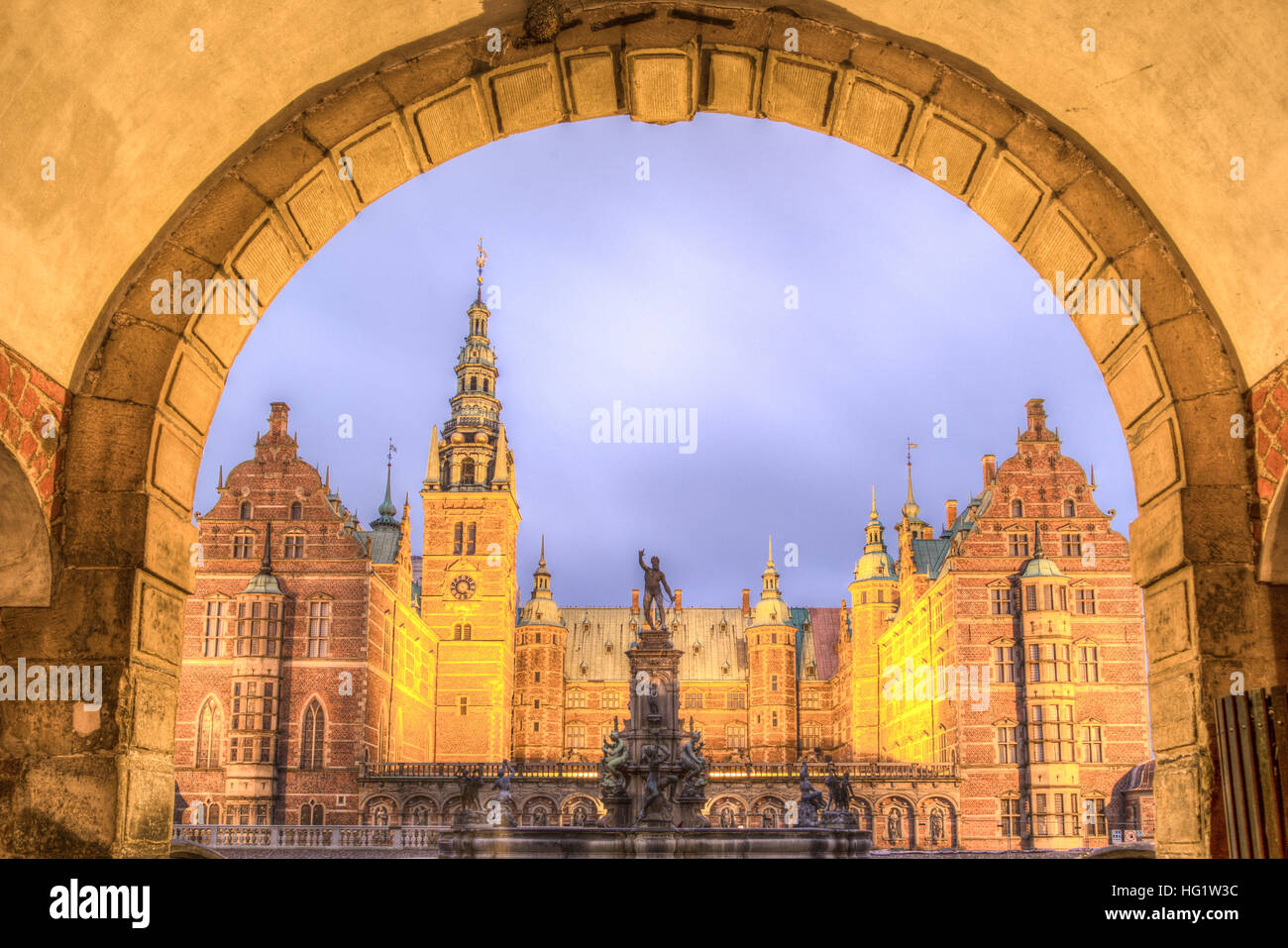 Hillerod, Denmark - December 29, 2016: View of the illuminated Frederiksborg Palace through an arch - Stock Image