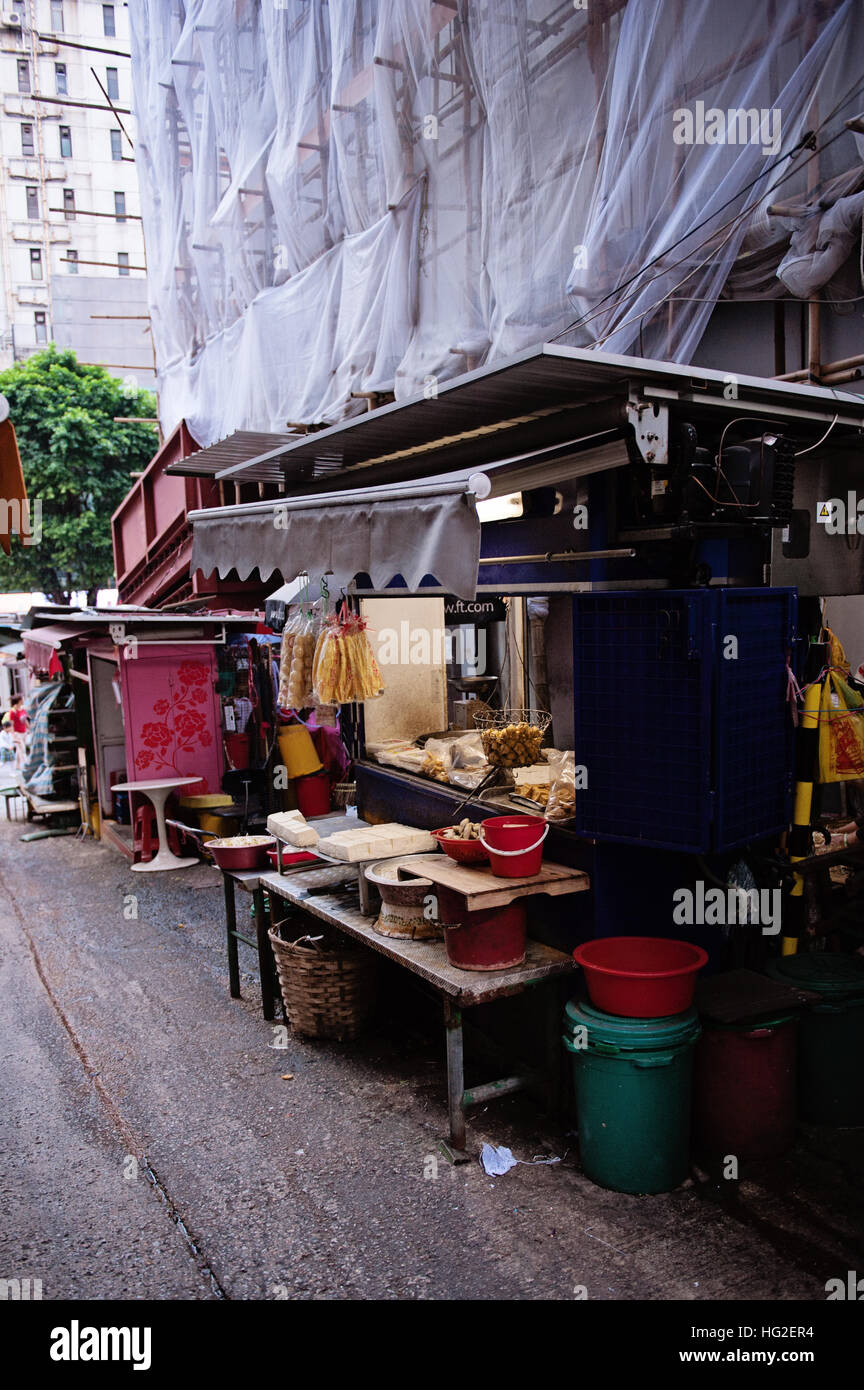 Hong Kong building with bamboo scaffolding and market stand Stock Photo
