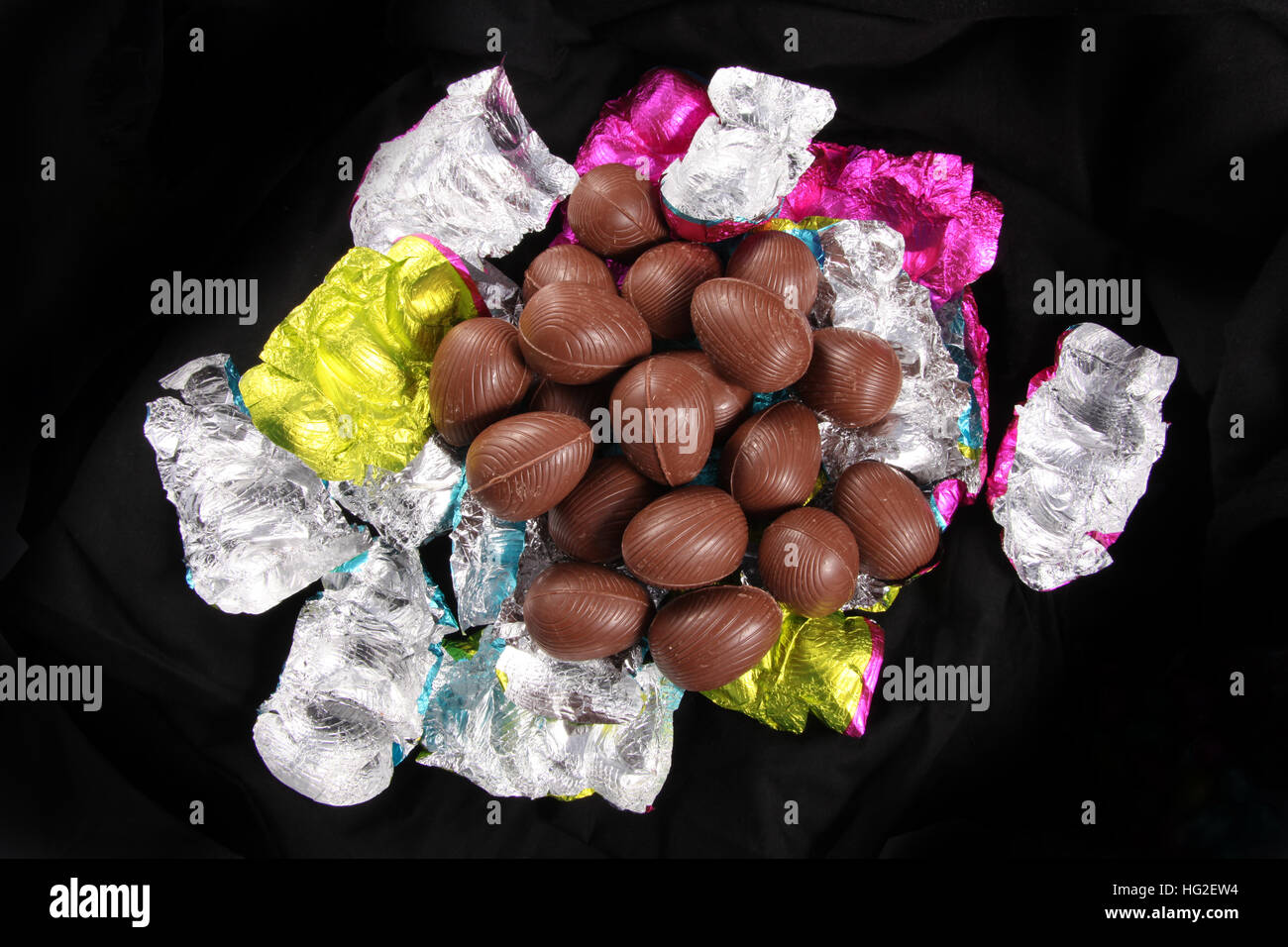 Pile of Chocolate easter eggs unwrapped from the colorful foil wrappers against a black background. - Stock Image