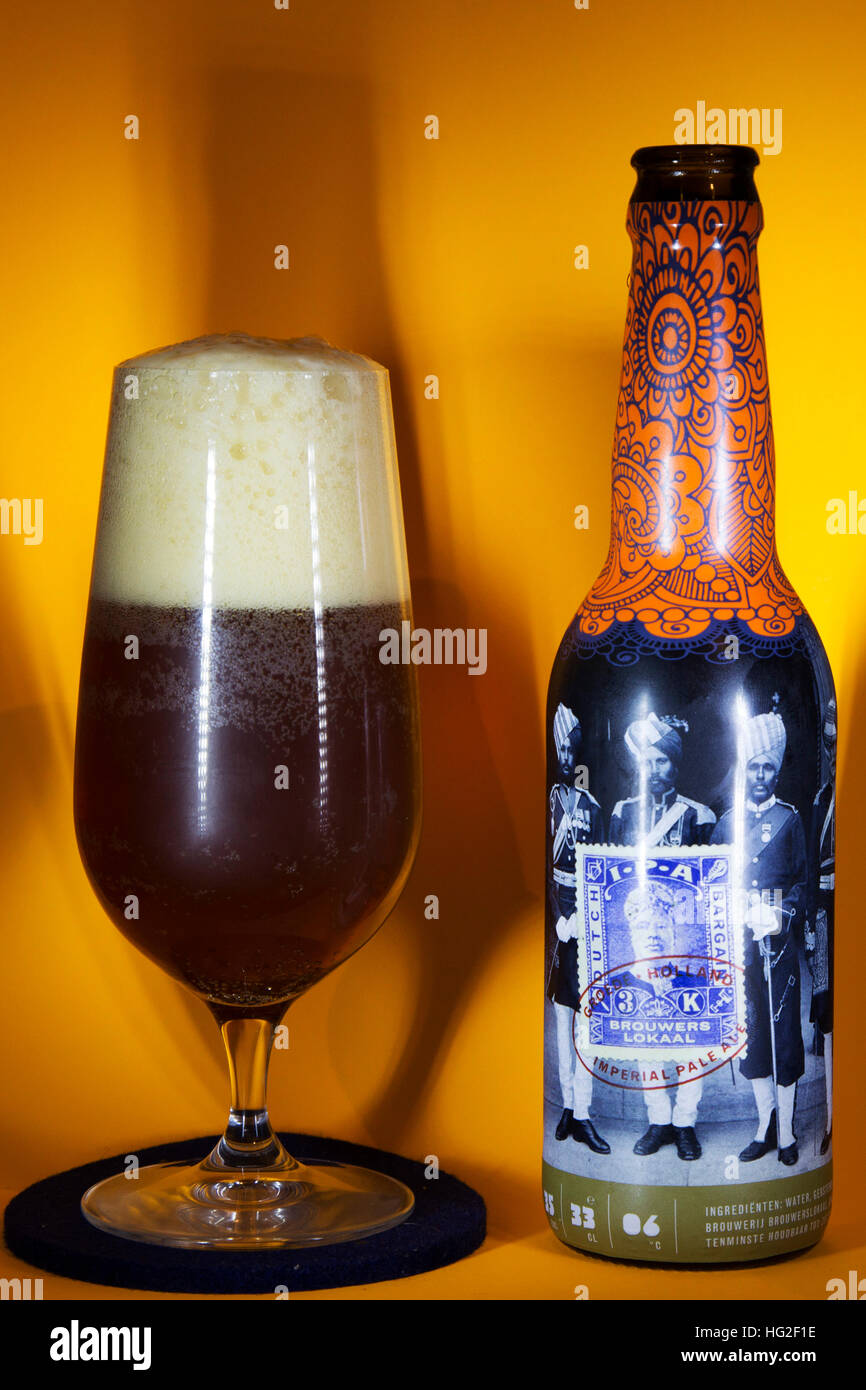 A bottle and glass of Brouwerslokaal Dutch Bargain IPA. The beer has ten per cent alcohol by volume. - Stock Image