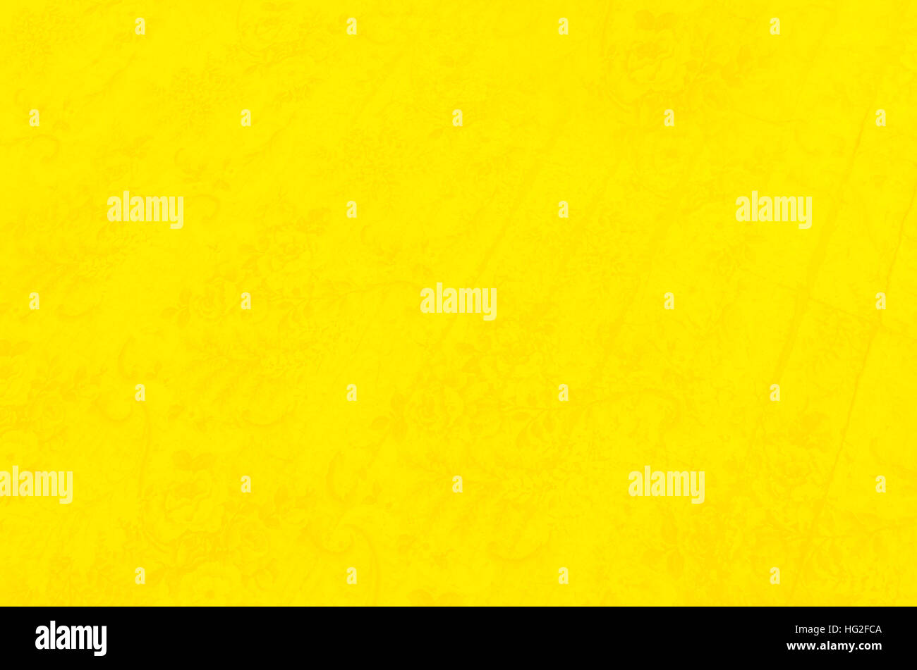 Bright, yellow background with a subtle flower pattern - Stock Image