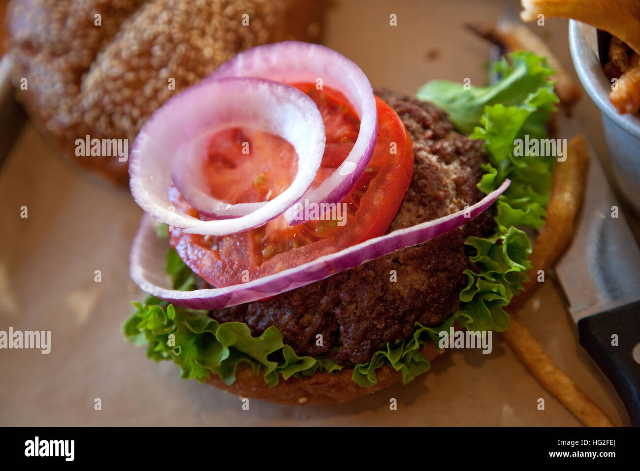 Delicious California Burger embellished with lettuce tomato and raw onion. St Paul Minnesota MN USA - Stock Image