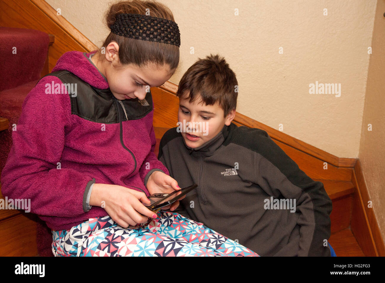 Girl and boy age 12 and 10 playing video game on small electronic handheld device. St Paul Minnesota MN USA Stock Photo