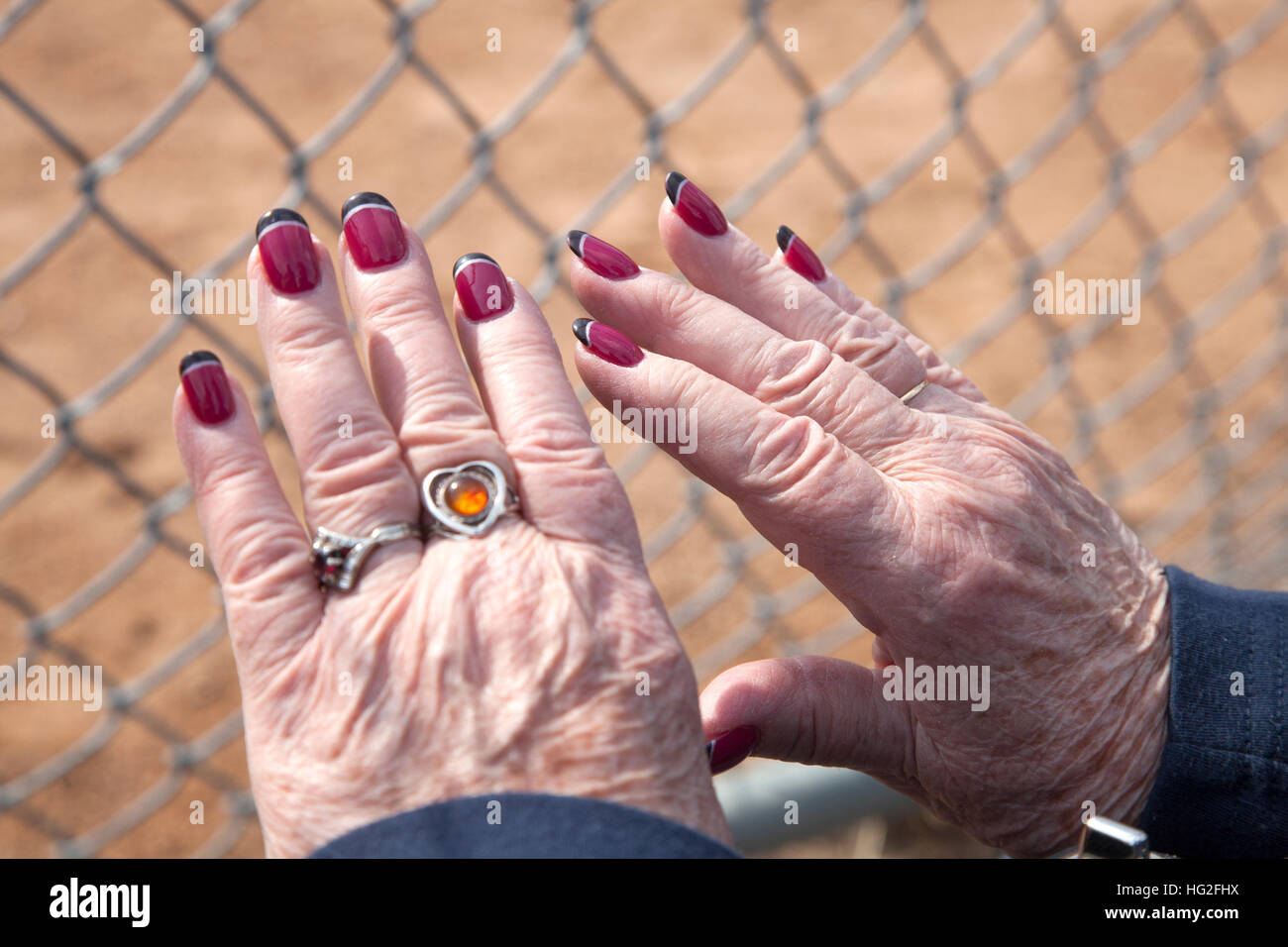Senior woman proudly showing off her latest red nails with black ...