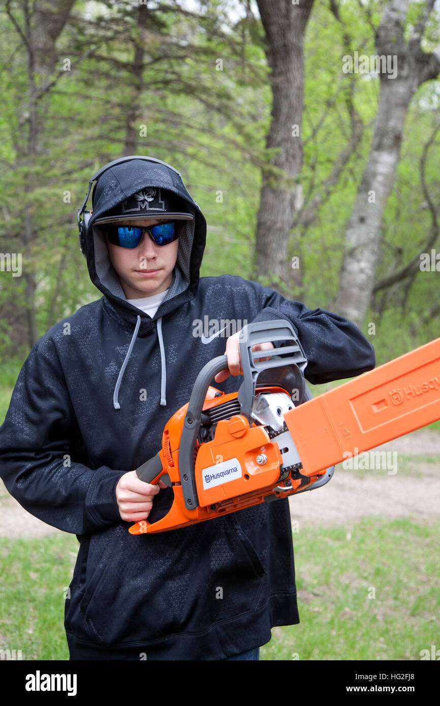 Teenage boy holding Husqvarna chainsaw ready to cut wood wearing safety glasses and ear protectors. Clitherall Minnesota - Stock Image