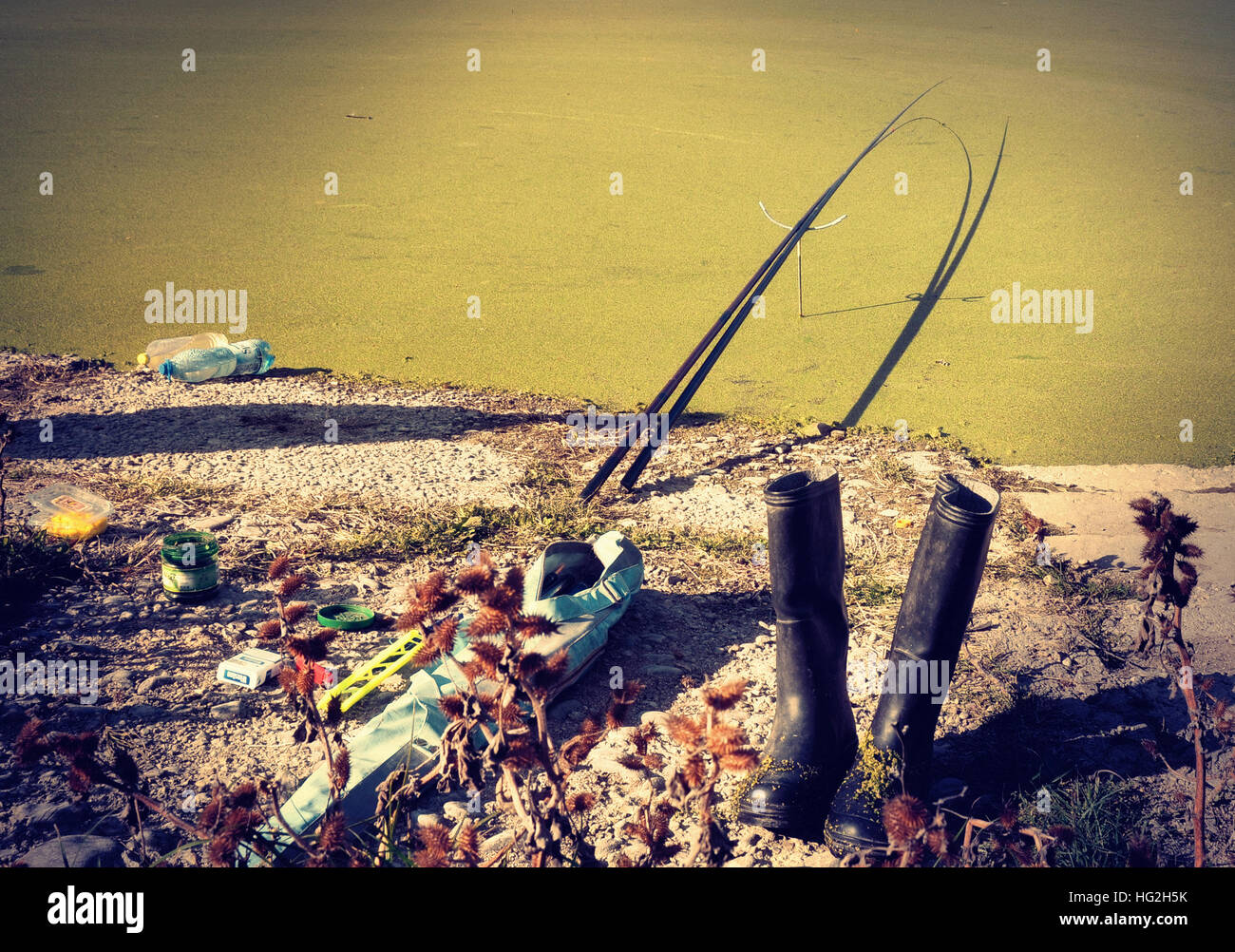 the accessories of the fisherman are on shore of a lake covered with moss but the fisherman himself is missing. - Stock Image