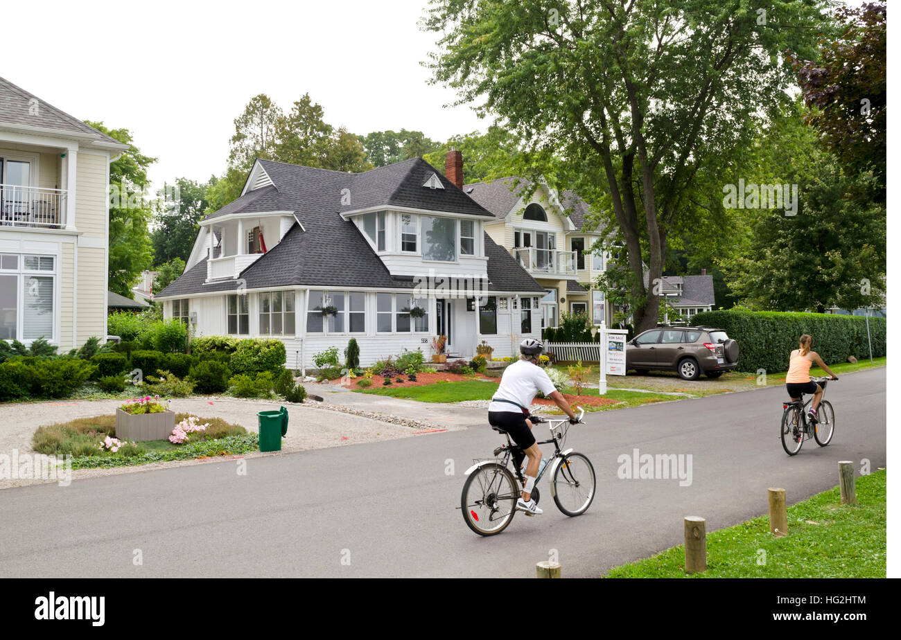 Two people cycling through a residential neighbourhood in Niagara-On-The-Lake in Ontario, Canada. - Stock Image