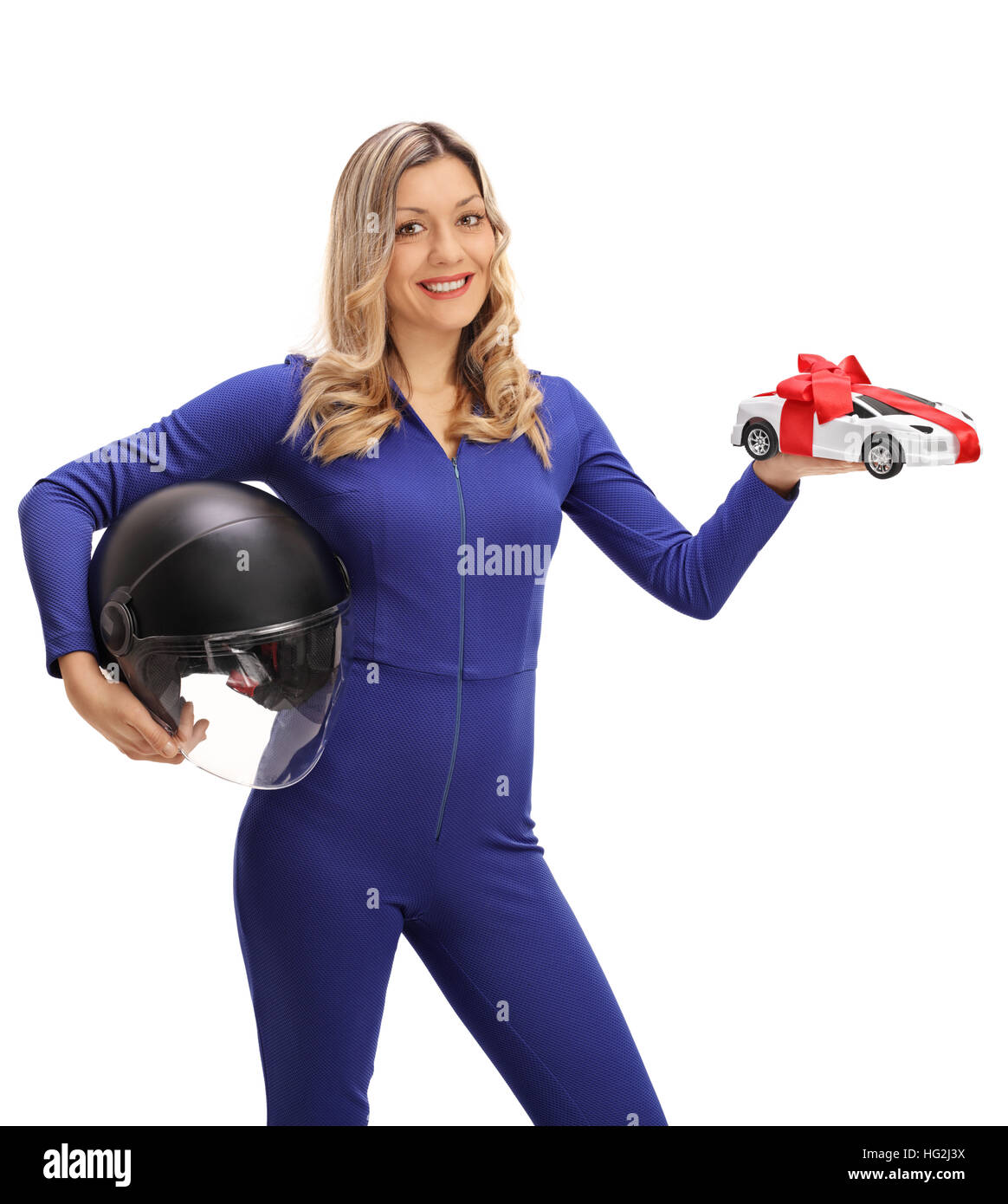 Happy female car racer holding a helmet and a model car isolated on white background - Stock Image