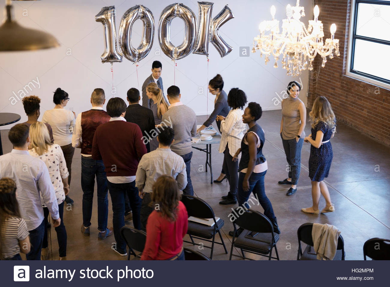 Business people networking celebrating milestone in conference room - Stock Image