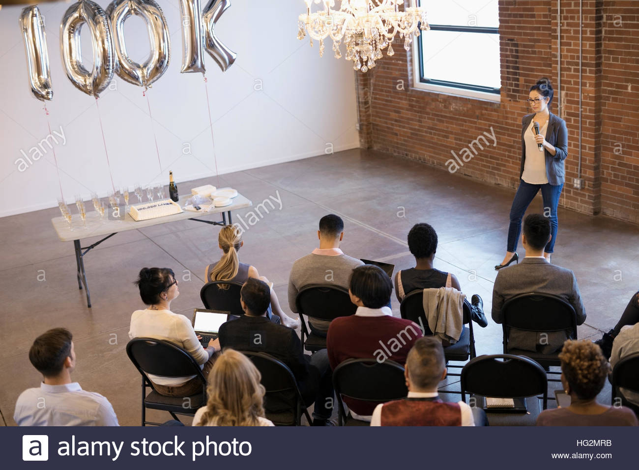 Businesswoman with microphone leading milestone conference meeting - Stock Image