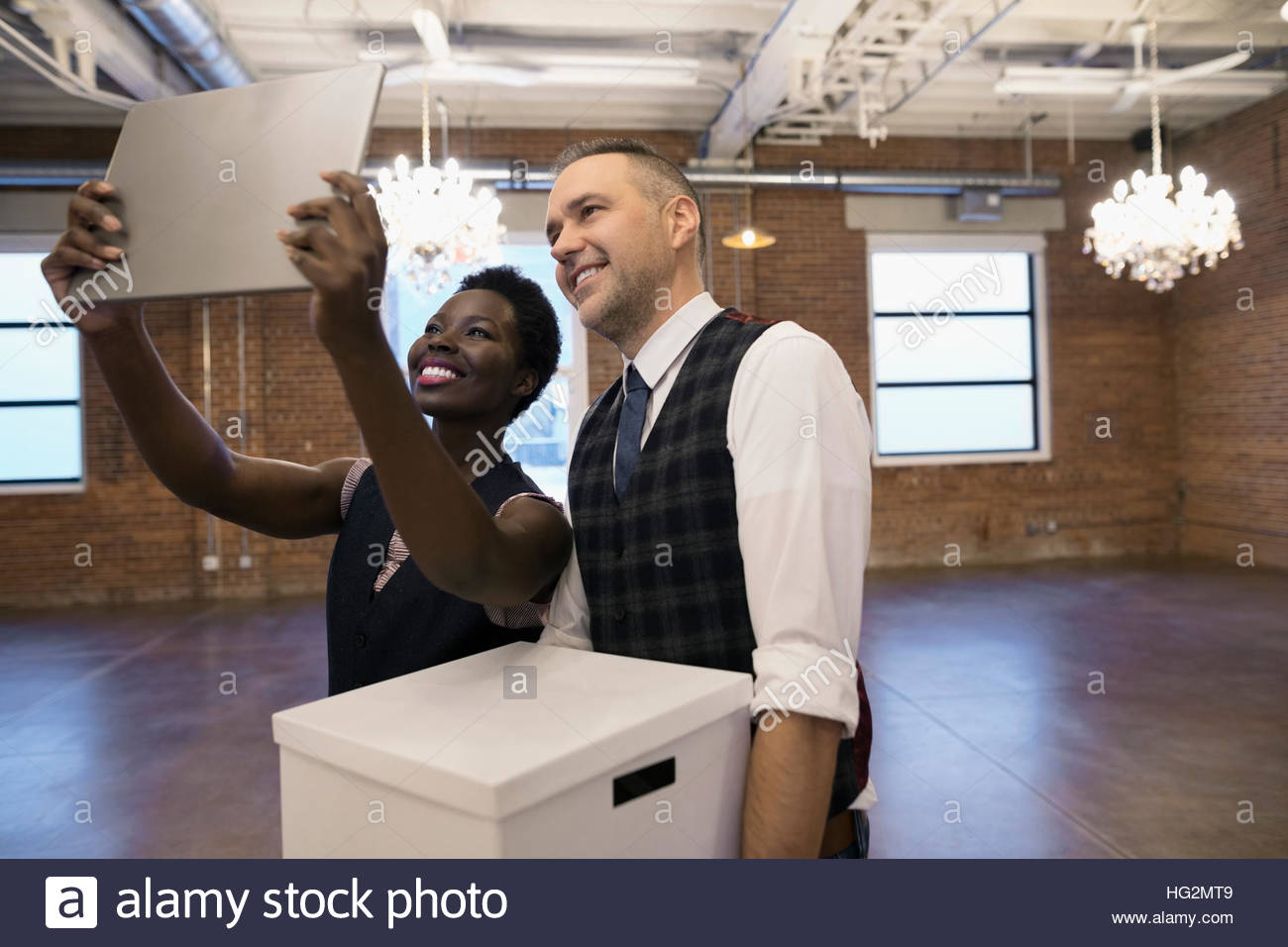 Businessman and businesswoman taking selfie with digital tablet camera in empty new office Stock Photo