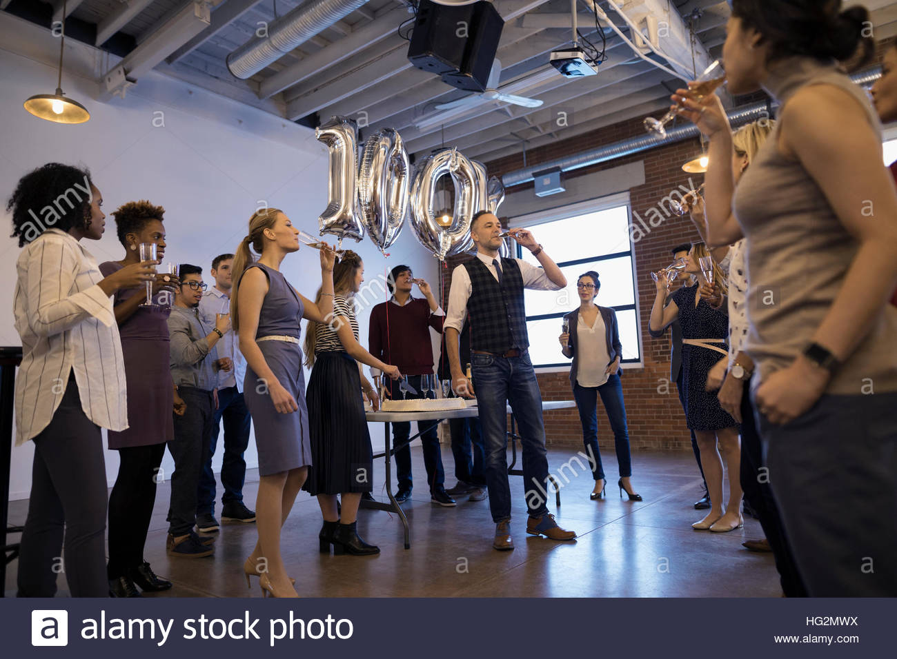 Business people celebrating milestone drinking champagne in conference room - Stock Image