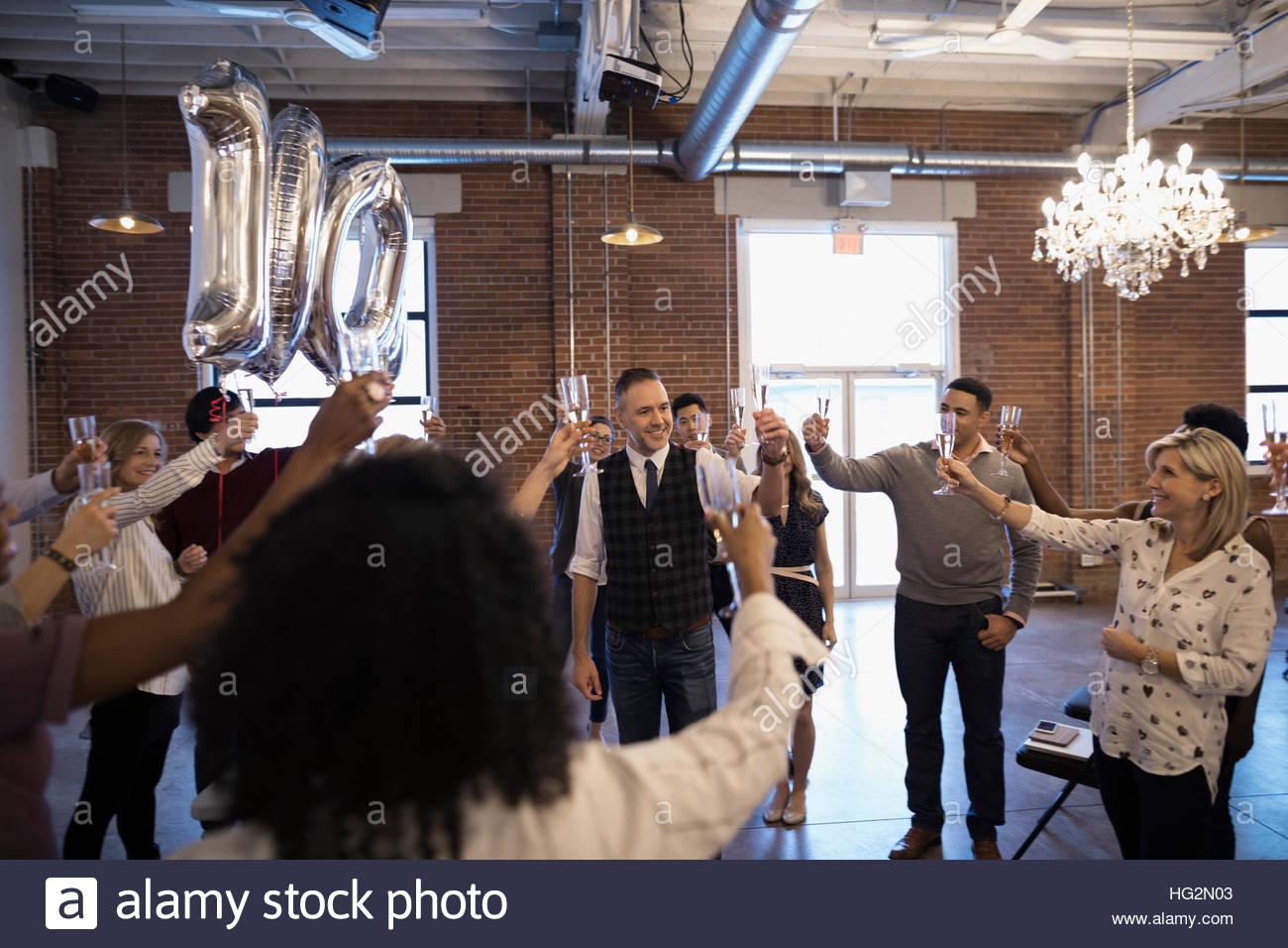 Business people celebrating milestone toasting champagne - Stock Image
