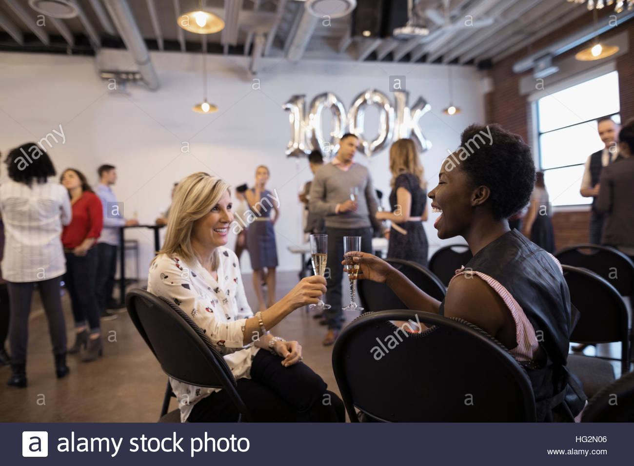 Businesswomen networking and celebrating milestone toasting champagne flutes - Stock Image