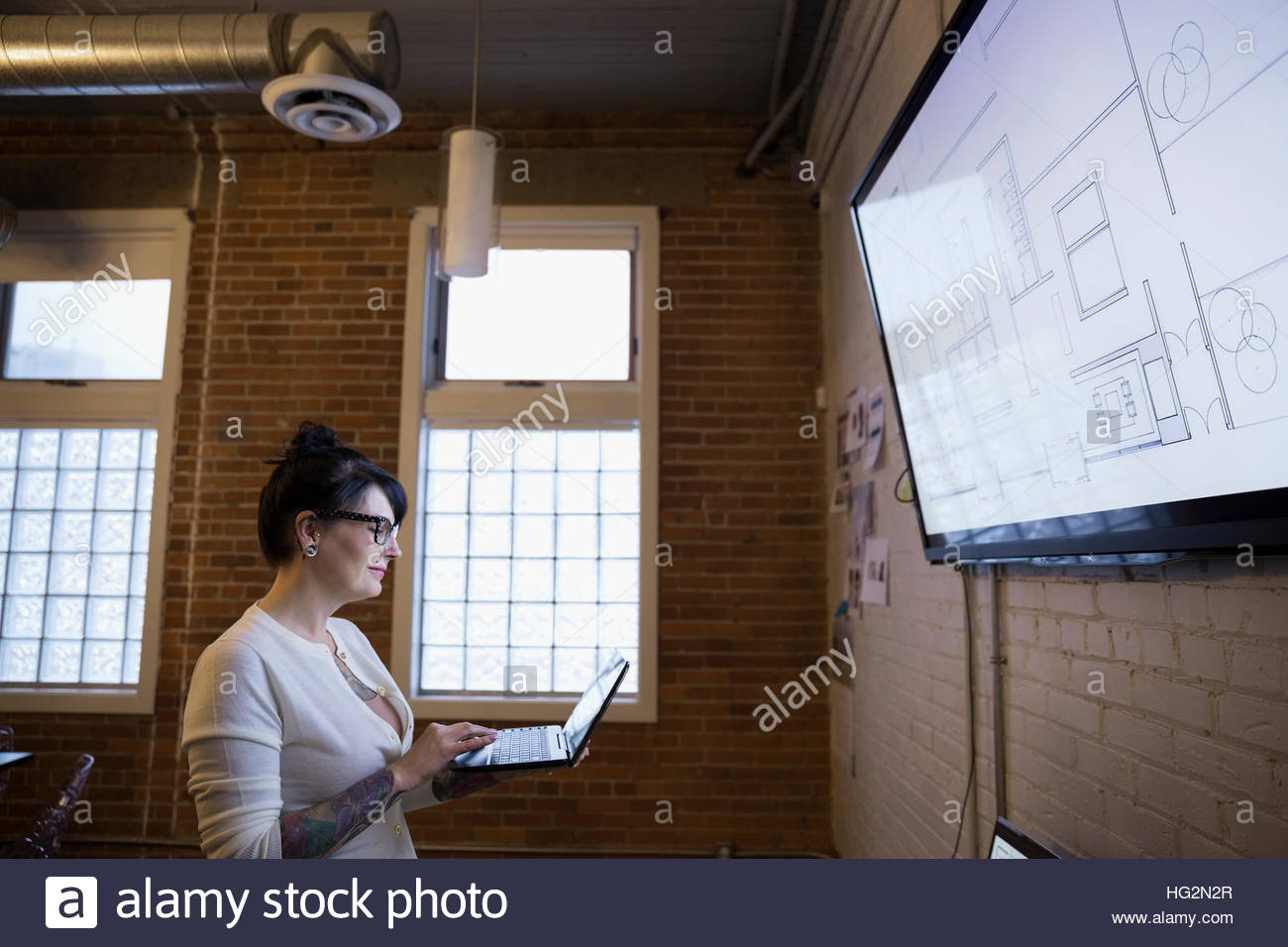 Female architect drafting digital blueprints on laptop at television monitor - Stock Image