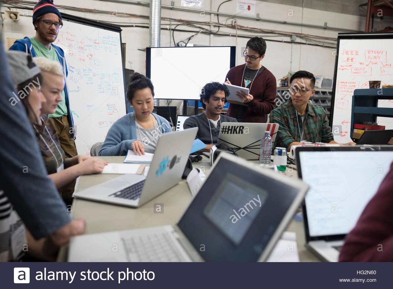 Hackers working hackathon at laptops in workshop - Stock Image