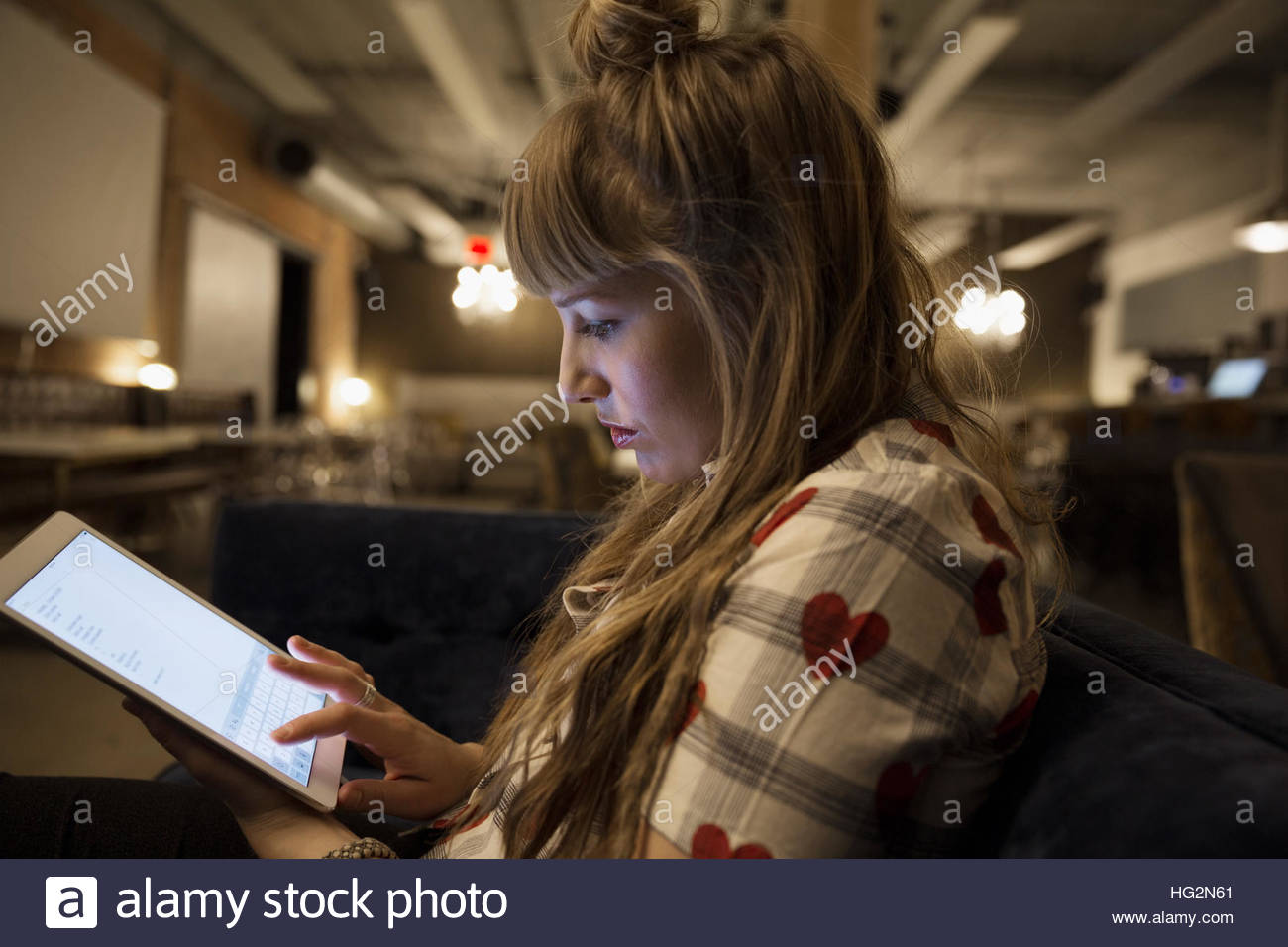 Focused businesswoman working late at digital tablet in office - Stock Image