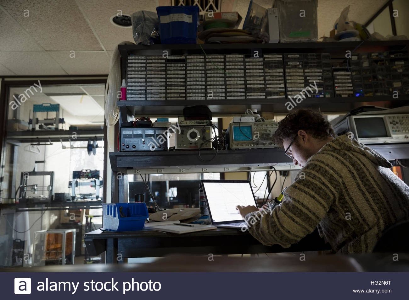 Computer programmer working at laptop in dark workshop - Stock Image