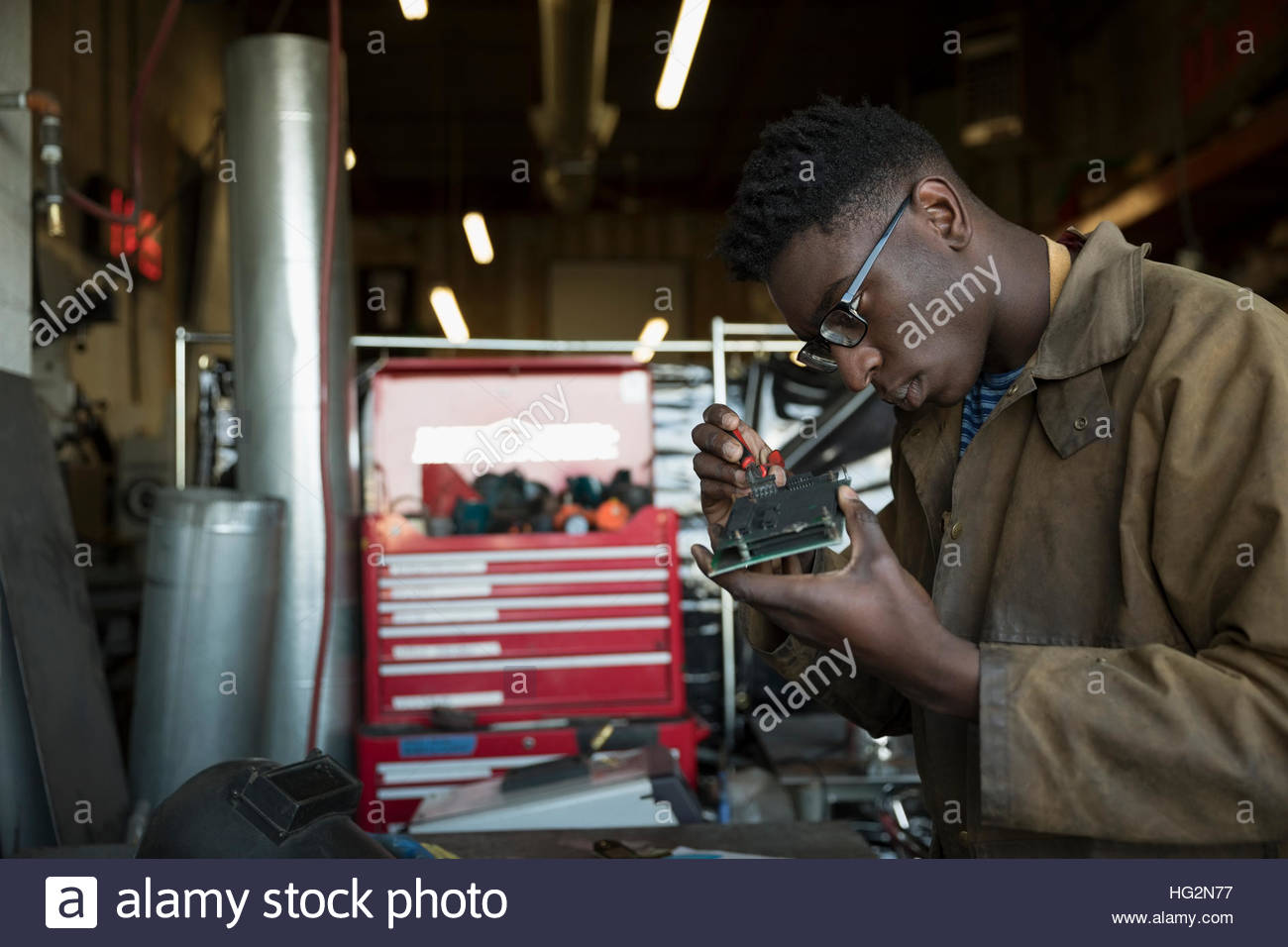 Engineer assembling electronics component in workshop - Stock Image