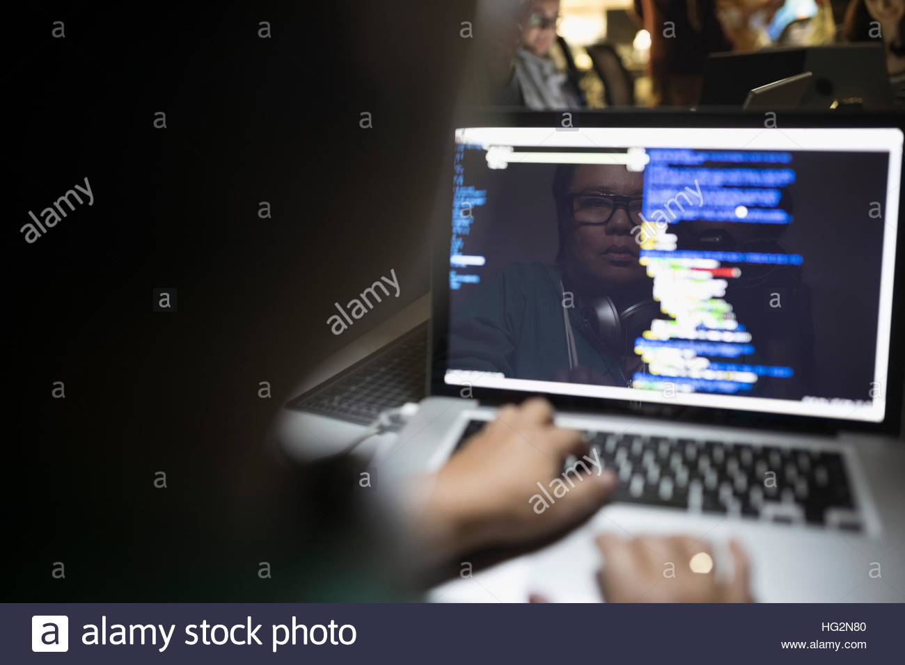 Reflection of female hacker coding working hackathon at laptop - Stock Image