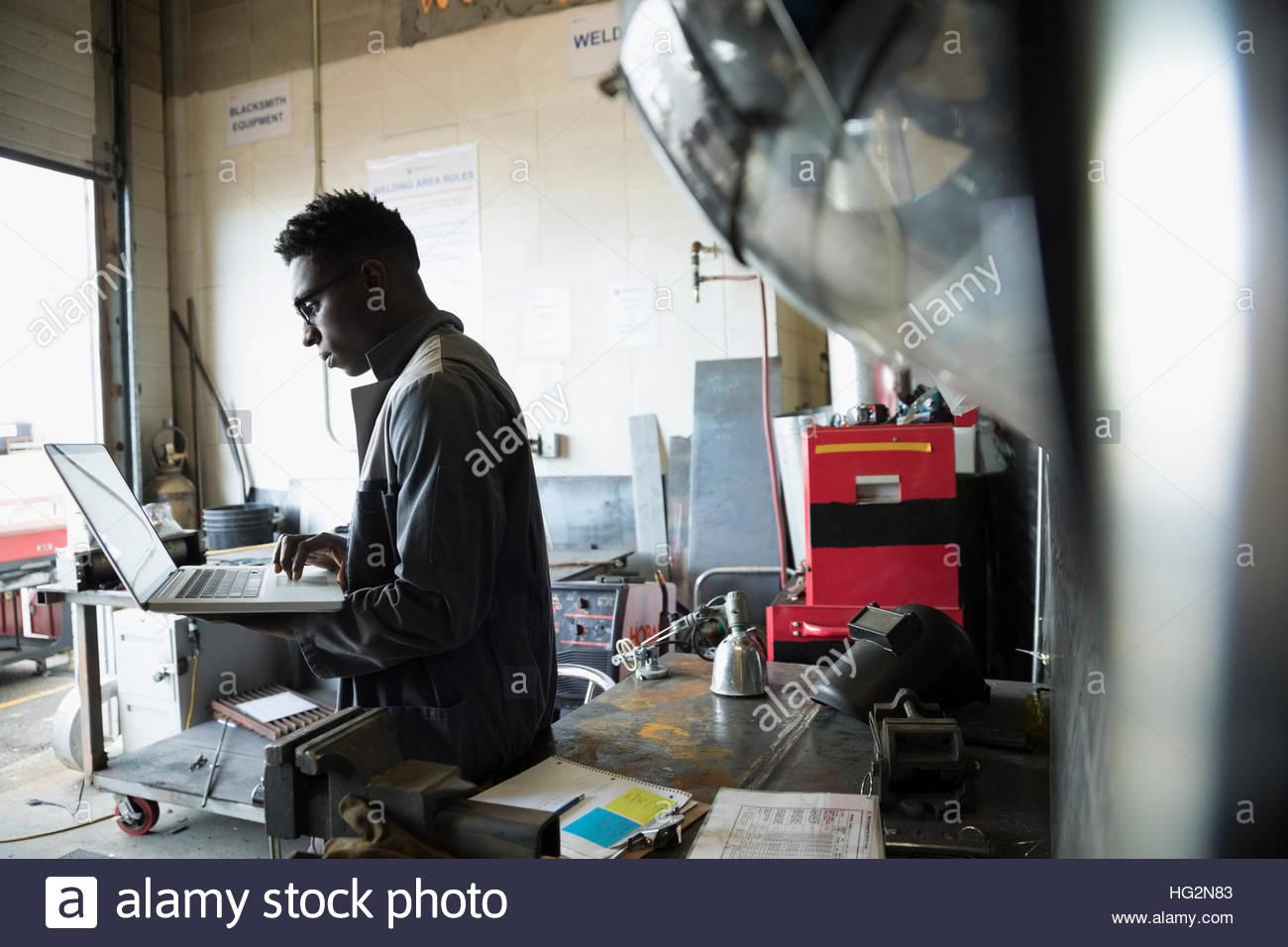Design professional engineer using laptop in workshop - Stock Image