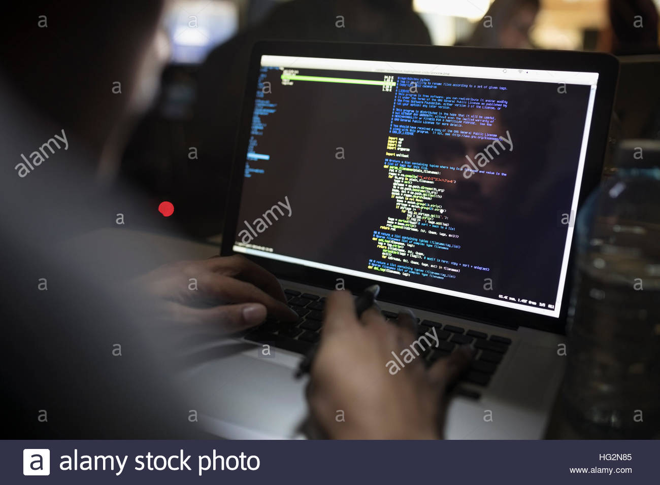 Reflection of male hacker coding working hackathon at laptop - Stock Image