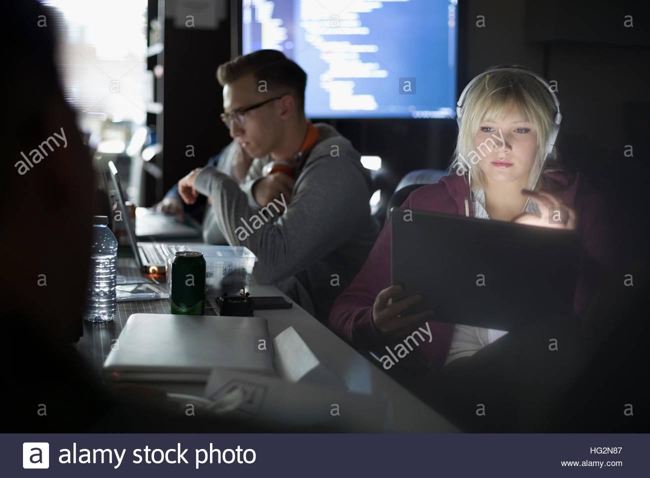 Focused female hacker working hackathon with laptop and headphones - Stock Image