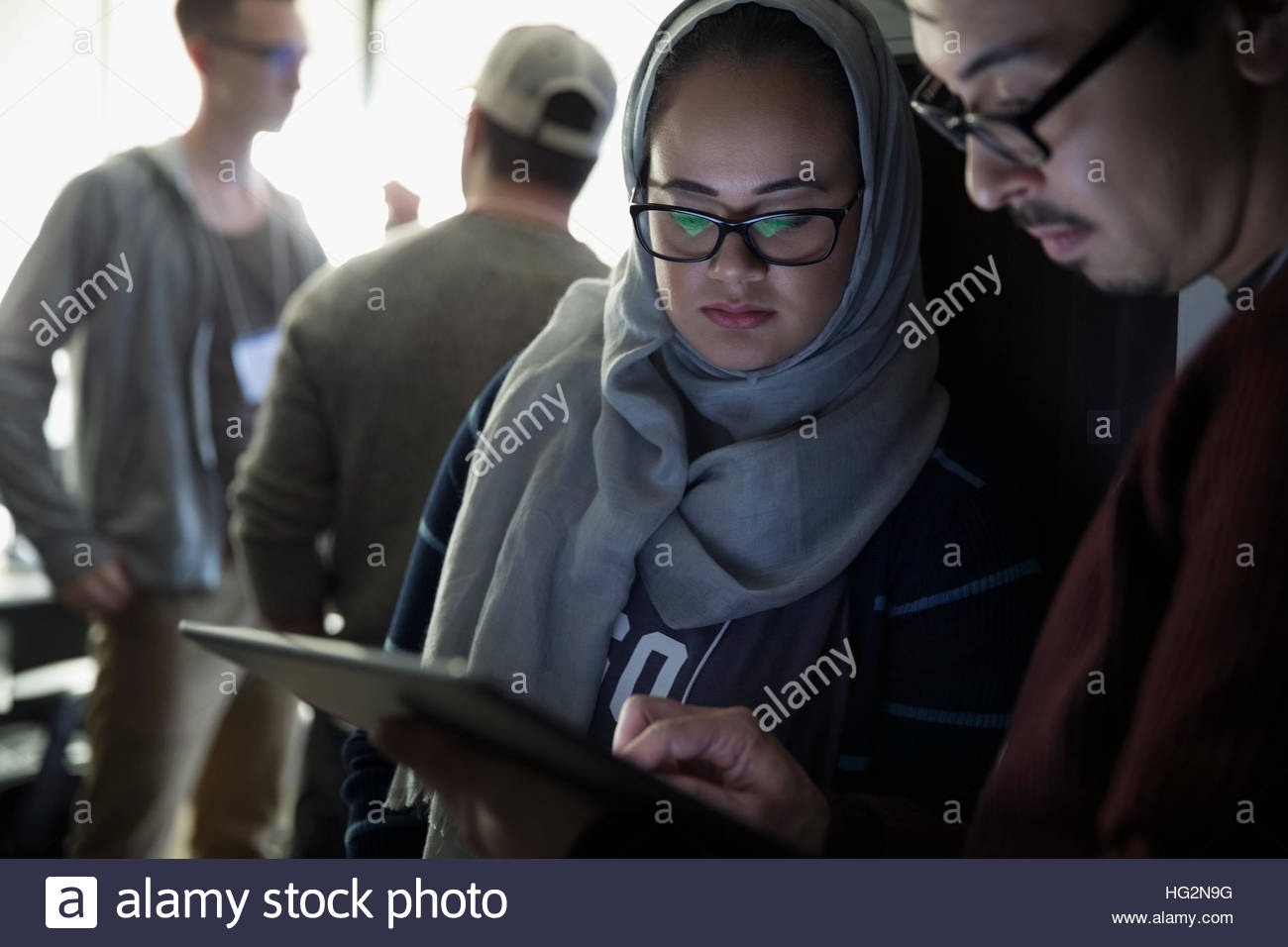 311740e6e8 Female hacker in hijab working with teammate at hackathon using digital  tablet - Stock Image