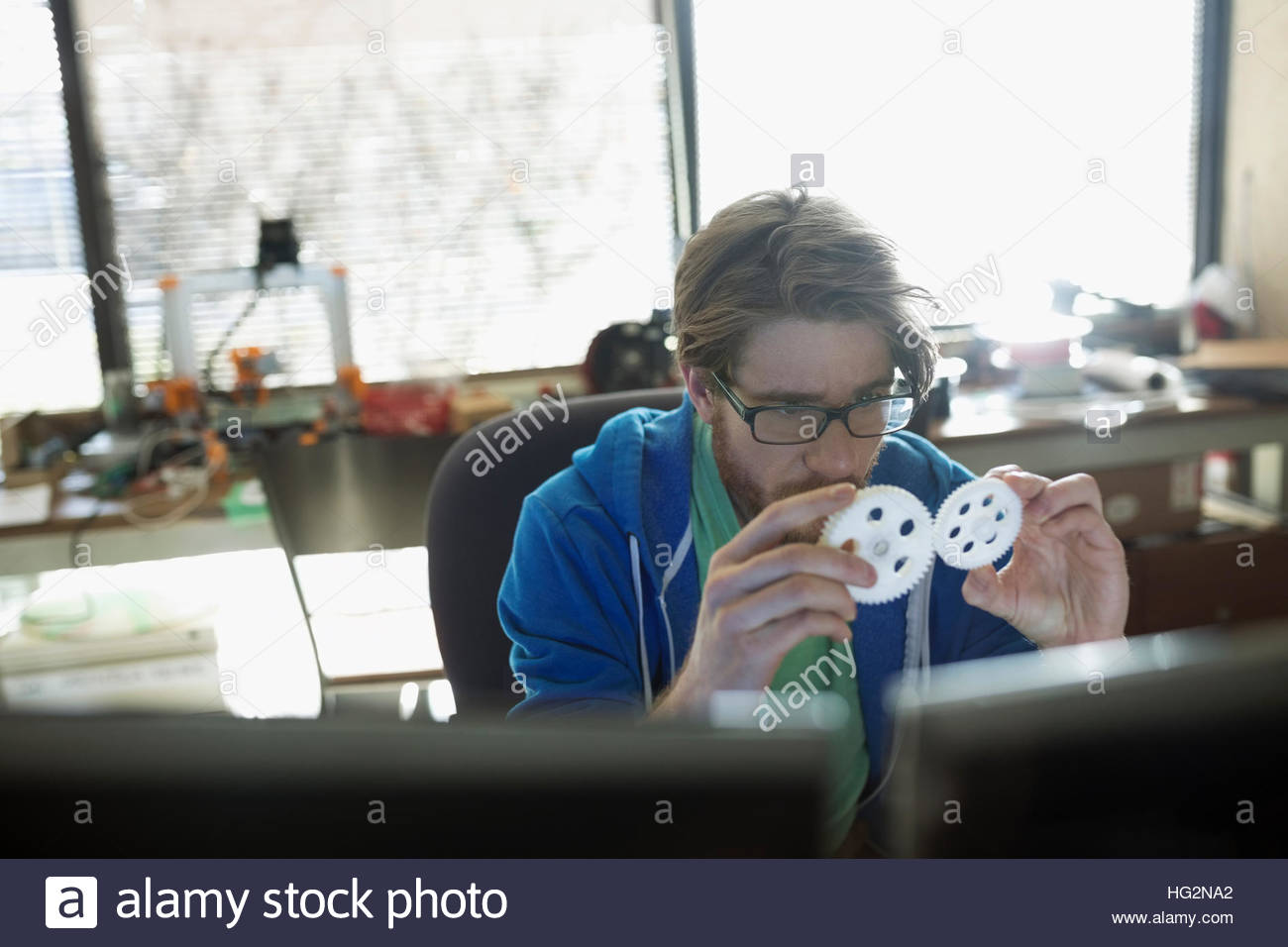 Male design professional engineer examining cogs in office - Stock Image