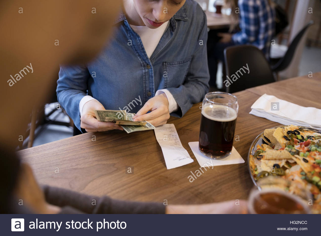 Woman with cash paying bill for beer in brewery restaurant - Stock Image