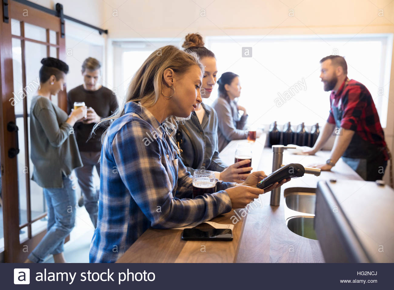 Female friends paying for beers using pin entry credit card reader at brewery tasting room bar - Stock Image