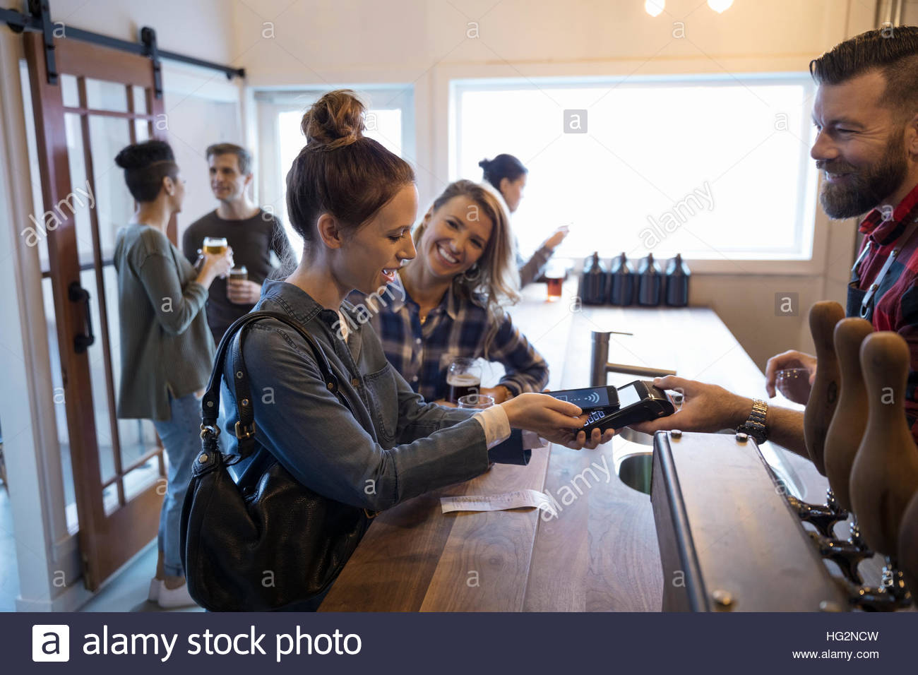 Female friends paying bartender for beers with smart phone contactless payment in brewery tasting room - Stock Image