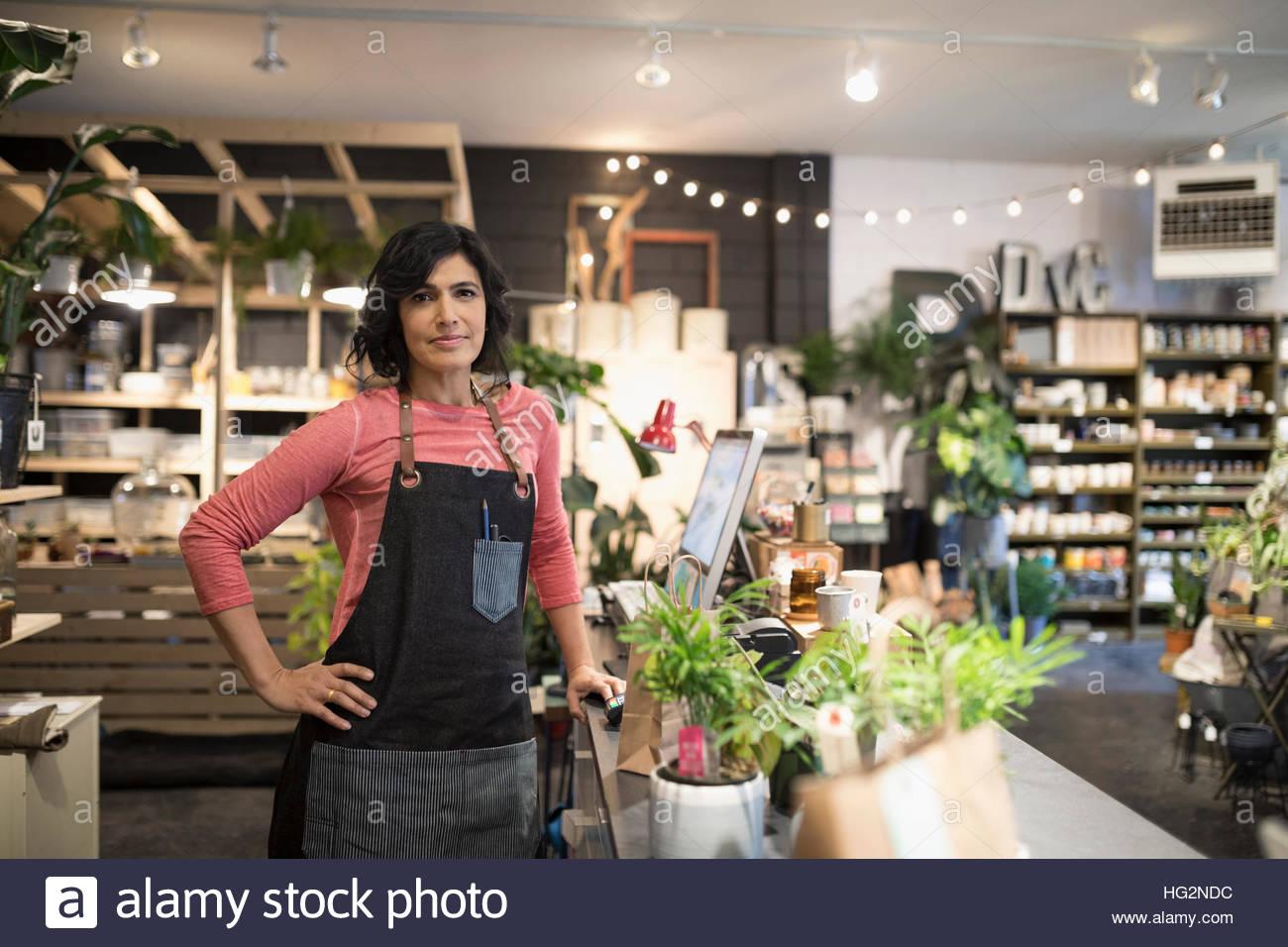 Portrait confident female shop owner in plant shop - Stock Image