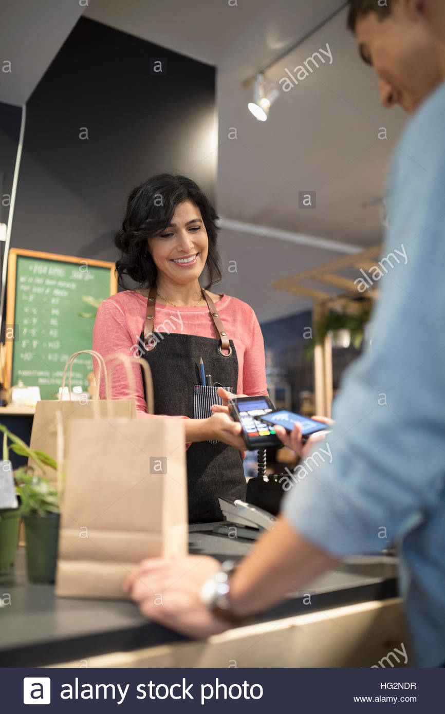 Female shop owner helping male customer paying with smart phone contactless payment at plant shop counter Stock Photo