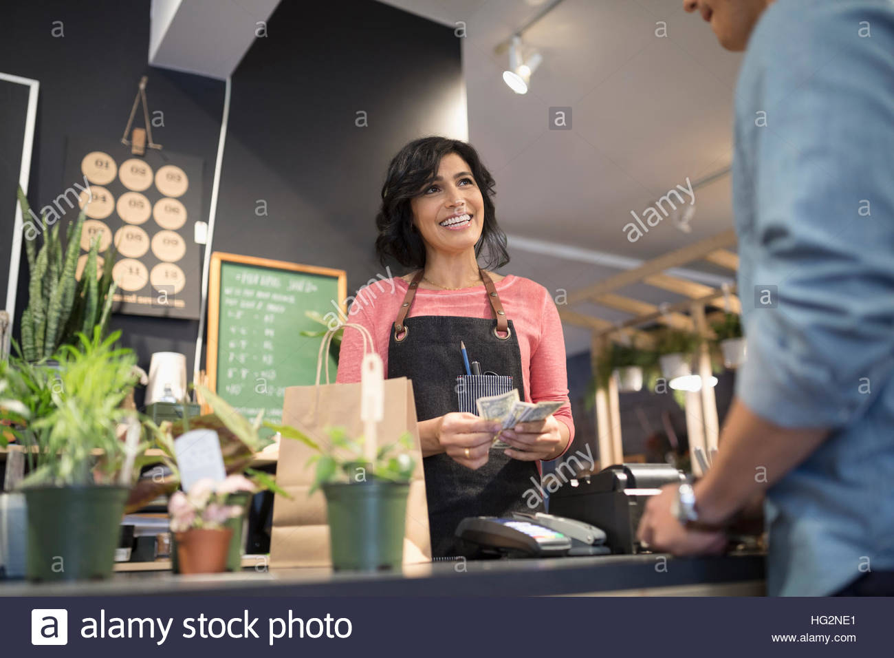 Female shop owner counting cash helping customer at plant shop counter - Stock Image