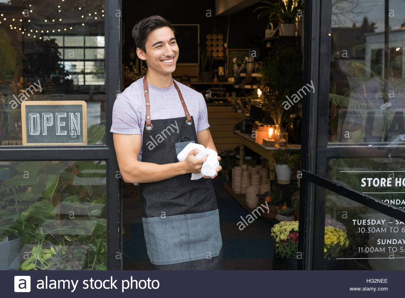 Smiling male shop owner looking away in doorway Stock Photo