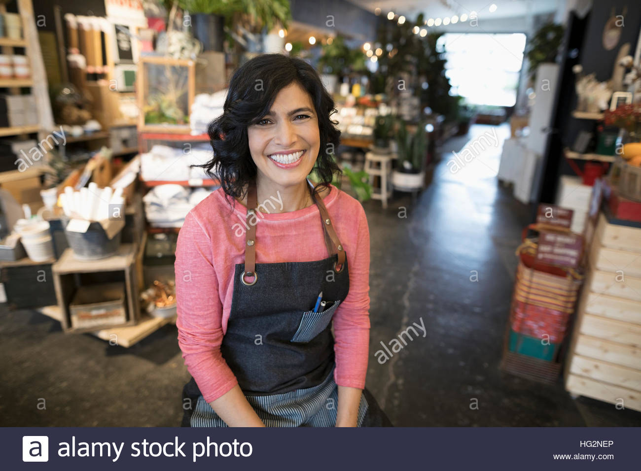 Portrait smiling enthusiastic female shop owner in plant shop - Stock Image