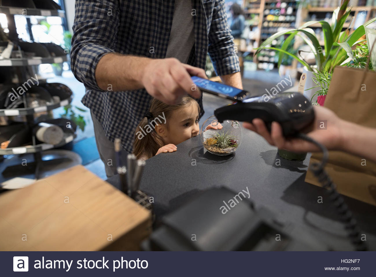 Close up father and daughter paying with smart phone contactless payment at plant shop counter - Stock Image