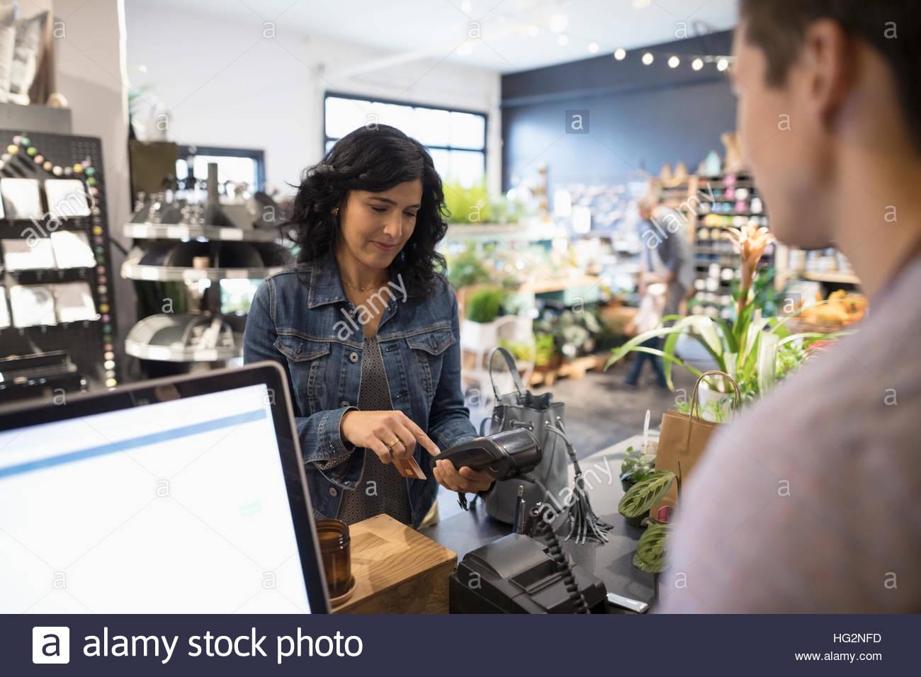 Female customer paying using pin entry credit card reader at plant shop counter - Stock Image