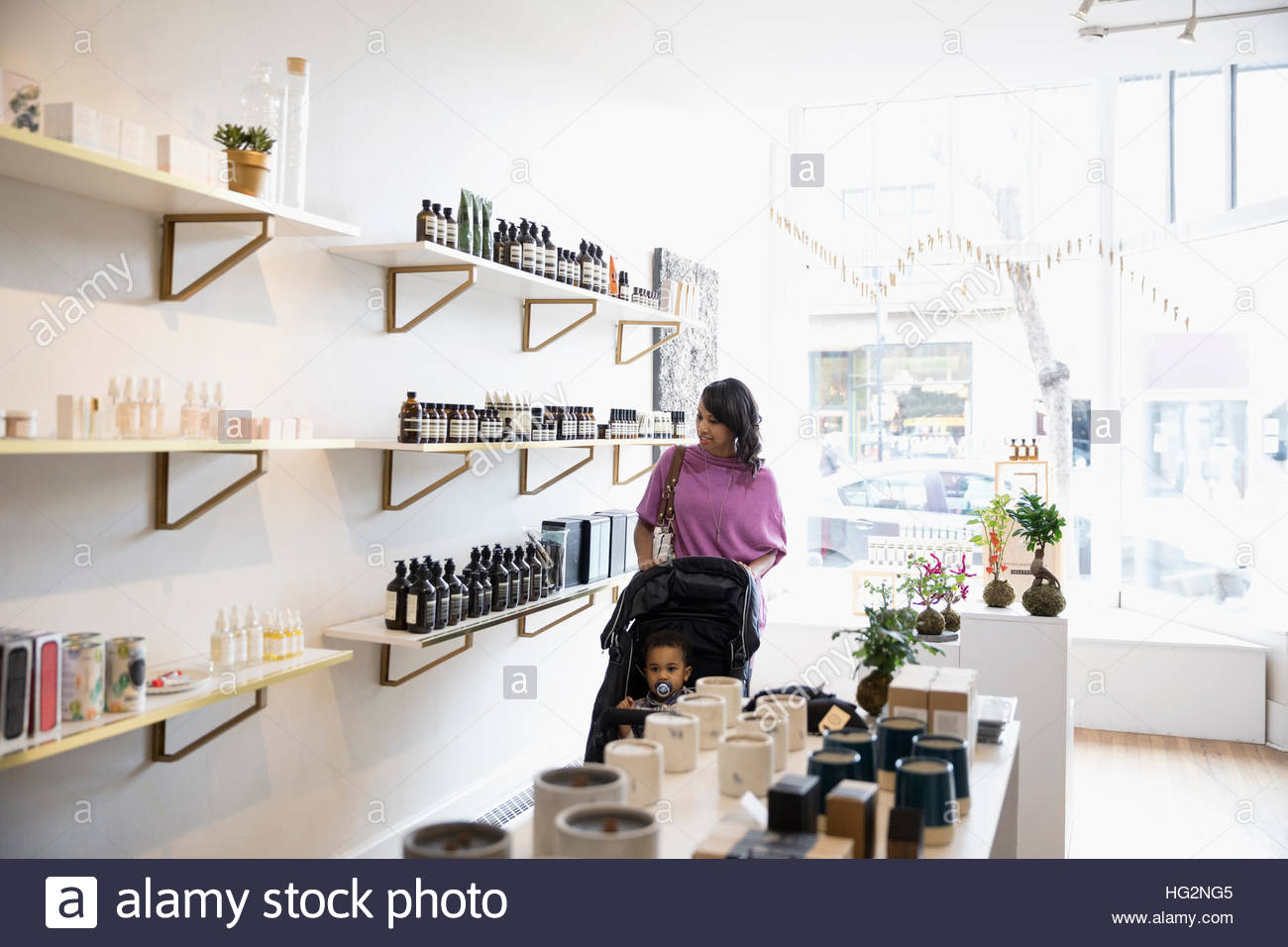 Mother and son shopping browsing merchandise on shelves in home fragrances shop - Stock Image