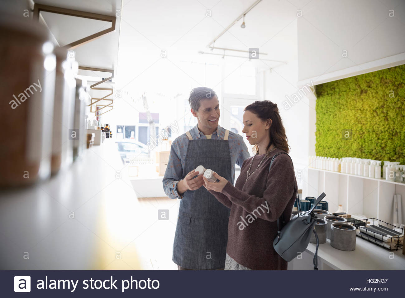 Male shop owner helping female customer shopping in home fragrances shop Stock Photo