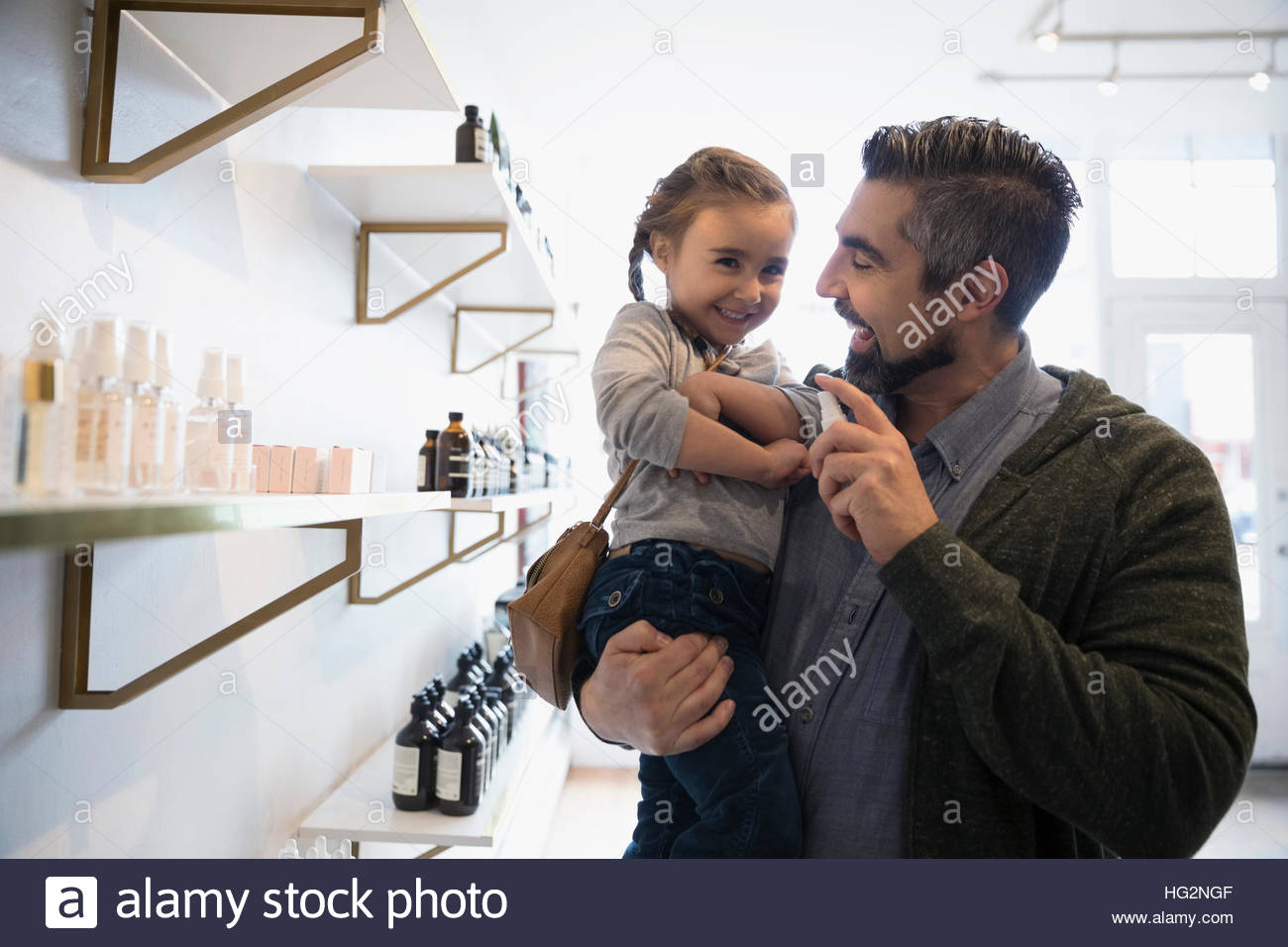 Father and daughter shopping spraying home fragrance in shop - Stock Image
