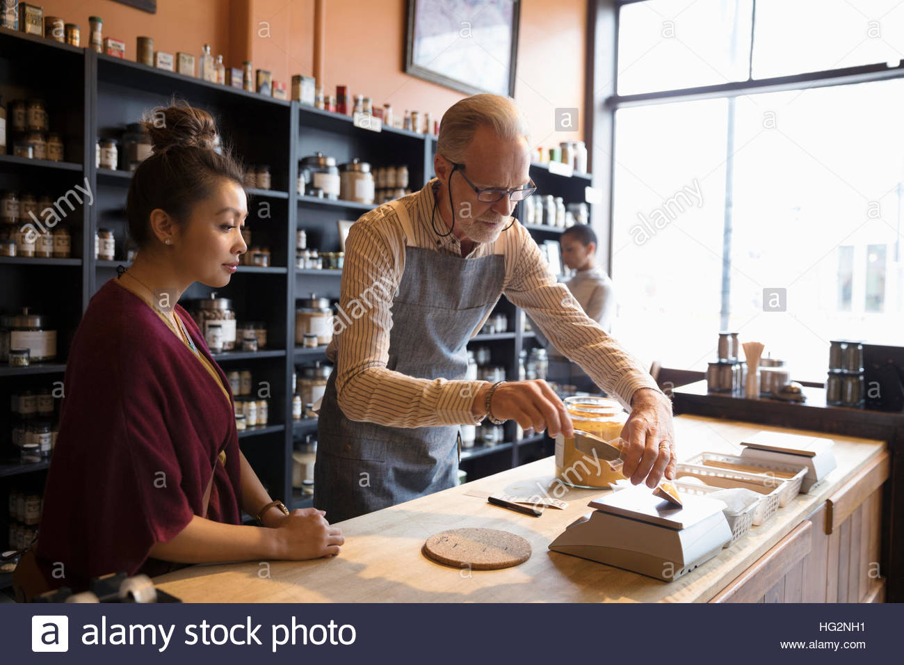 Male shop owner scooping and weighing saffron for female customer at counter - Stock Image