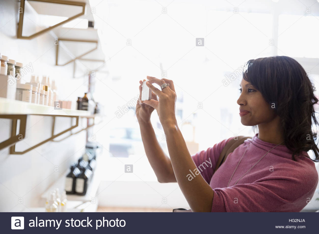 Woman with camera phone photographing merchandise on shelves in home fragrances shop - Stock Image