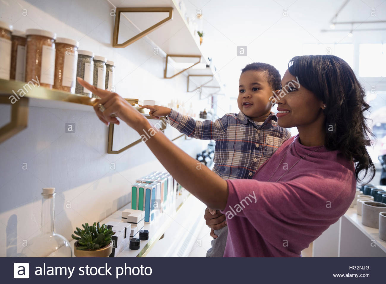 Mother and son browsing merchandise on shelf in shop Stock Photo