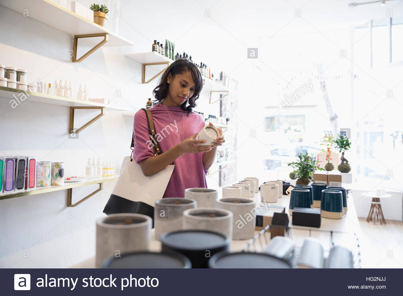 Woman shopping browsing candles in home fragrances shop - Stock Image