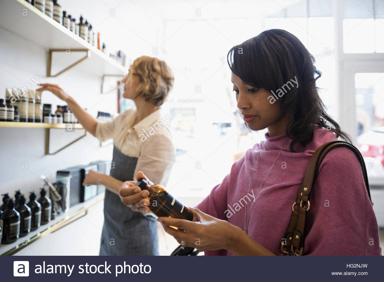 Woman shopping browsing beauty products in shop - Stock Image