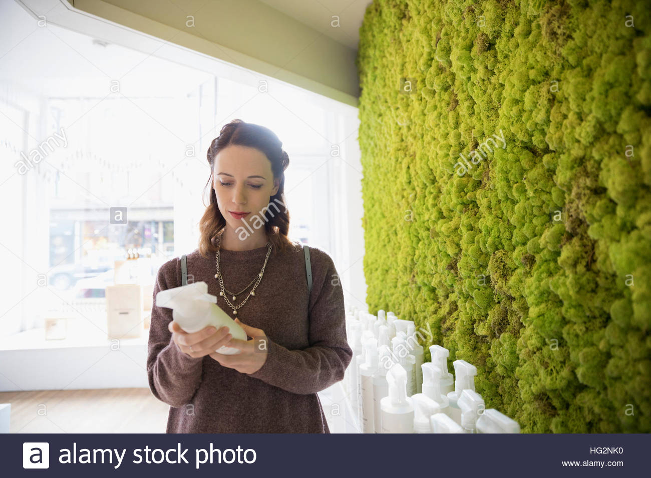 Woman shopping browsing cleaners in home goods shop - Stock Image
