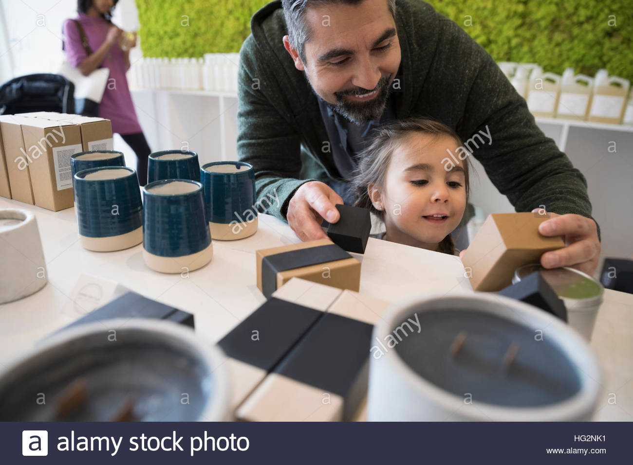 Father and curious daughter browsing home fragrances in shop - Stock Image
